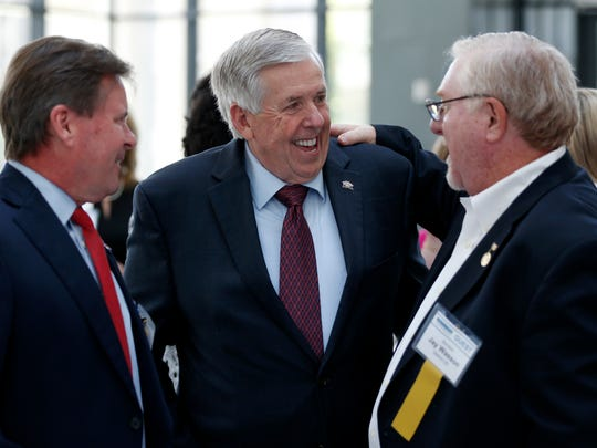 Missouri Gov. Mike Parson laughs with then-Sen. Jay Wasson (right) and then-Rep. Kevin Austin at the Springfield Metro Partnership event in in 2018.