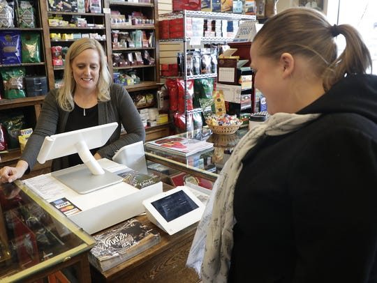 Amy Warmenhoven, right, completes a transaction on