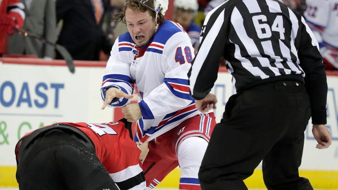 New York Rangers left wing Brendan Lemieux (48) fights with New Jersey Devils left wing Miles Wood, left, as linesman Brandon Gawryletz (64) looks on during the second period of an NHL hockey game, Monday, April 1, 2019, in Newark, N.J. (AP Photo/Julio Cortez)