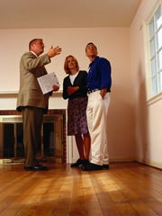 A real estate agent shows a couple a house. Presenting the best qualities of a house is important when a home lingers for sale longer than the seller hoped.