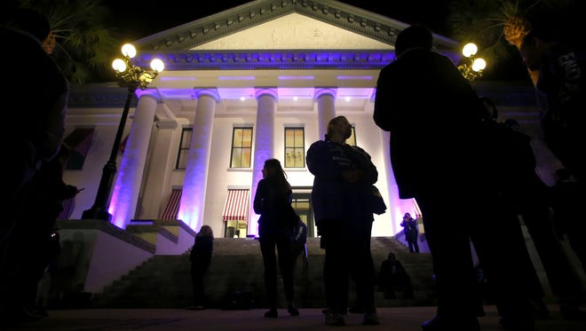 Members of the Southeast Florida Chapter of the Alzheimer's Association stand outside the Historic Capitol on Tuesday evening. The building was lit purple to honor the more than 500,000 Floridians with the disease.
