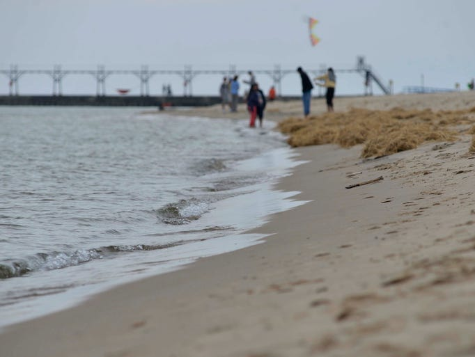 People walk along the beach at Grand Haven State Park