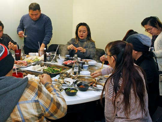 Family and friends do hot pot and Korean barbecue in between singing karaoke on Monday, April 16, 2018 at Huan Xi. They were celebrating a family reunion. Similar karaoke rooms are really popular in Korea and throughout Asia. Angela Peterson/Milwaukee Journal Sentinel