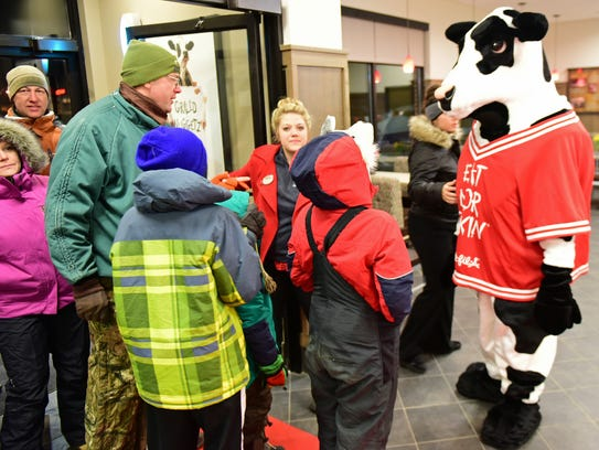 The Chick-fil-A mascot greets customers early Thursday