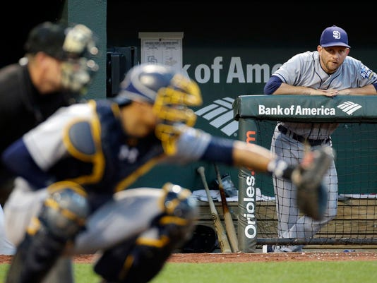 San Diego Padres manager Andy Green, right, is seen past Padres catcher Christian Bethancourt and home plate umpire Jerry Meals as he watches from the dugout in the fourth inning of an interleague baseball game against the Baltimore Orioles in Baltimore, Wednesday, June 22, 2016. (AP Photo/Patrick Semansky)