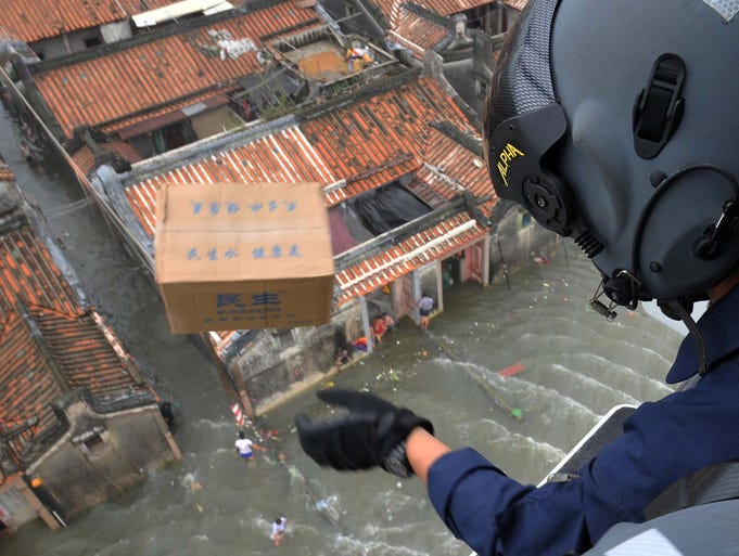 A rescue worker drops a box of food from a helicopter to flood victims on Aug. 21 in Shantou, Guangdong province, China. The death toll has risen to 130 people from devastating floods at opposite ends of the country.