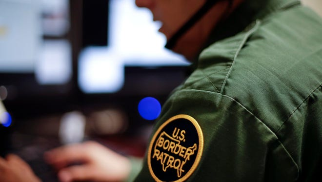 In this June 5, 2014 photo, a Border Patrol agent uses a headset and computer to conduct a long distance interview by video with a person arrested crossing the border in Texas, from a facility in San Diego. (AP Photo/Gregory Bull)