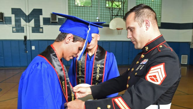 From left, Conner Blake receives a sash from Marine Corps Staff Sergeant Joshua Buteau prior to the start of Friday's commencement at Millbrook High School. Connor Blake, and Jacob Coy, in the background, are joining the Marine Corps after graduation.