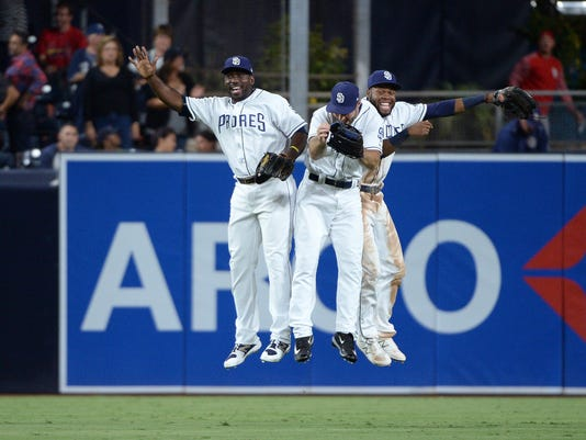 San Diego Padres' Jose Pirela, Matt Szczur and Manuel Margot, from left, celebrate in the outfield after the Padres defeated the St. Louis Cardinals 3-0 in a baseball game Thursday, Sept. 7, 2017, in San Diego. (AP Photo/Orlando Ramirez)