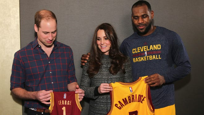 Prince William, Duchess Kate and LeBron James pose backstage at NBA game in Brooklyn on Dec. 8, holding gifts for Prince George.
