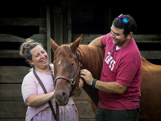 In this Thursday, Aug. 11, 2016 photo, Joe Forzano and his wife Sami Forzano pet their one-eyed horse Baxter at the farm in Loxahatchee, Fla. The couple care for the horse after their dear friend and colleague, Pat Stephens, who owned the horse died from cancer in April, 2016.