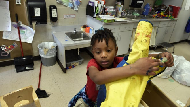 Jayda Edwards 4, puts away her painting smock at the Bordeaux Early Learning Center Thursday March 17, 2016, in Nashville, Tenn. Her mother Joy Edwards is a part of the Parents as Partners Program at the education center.