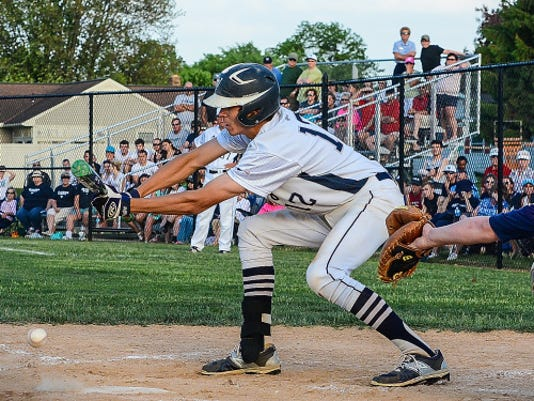 West York's Cash Gladfelter lays down a perfect suicide squeeze bunt to score teammate Brandon Sheffer with the winning run on Tuesday. Tuesday May 12, 2015.