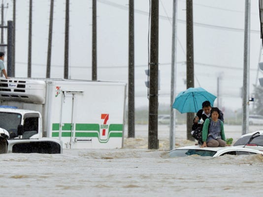 People wait for help as the vehicles are submerged in flooding in Joso, Ibaraki prefecture, northeast of Tokyo Thursday, Sept. 10, 2015. Heavy rain is pummeling Japan for a second straight day, overflowing rivers and causing landslides and localized flooding in the eastern part of the country. (Kyodo News via AP)