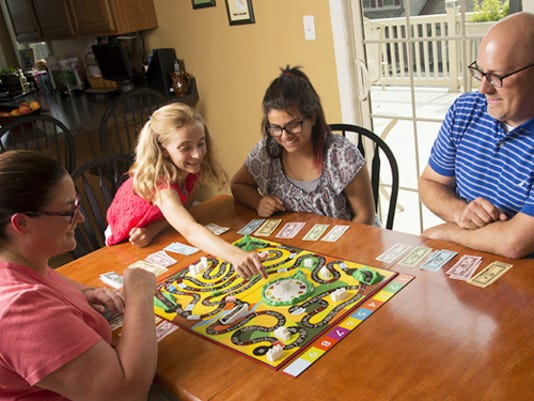 The Uhlers, from left, Angela, Grace, Tori and Jeff, play a game at their Windsor Township home.