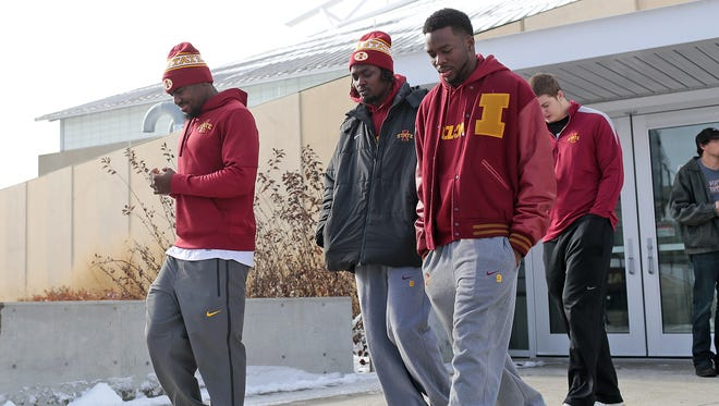 Iowa State football players walk to the Jacobson Building after leaving a meeting about the firing of head coach Paul Rhoads Sunday.