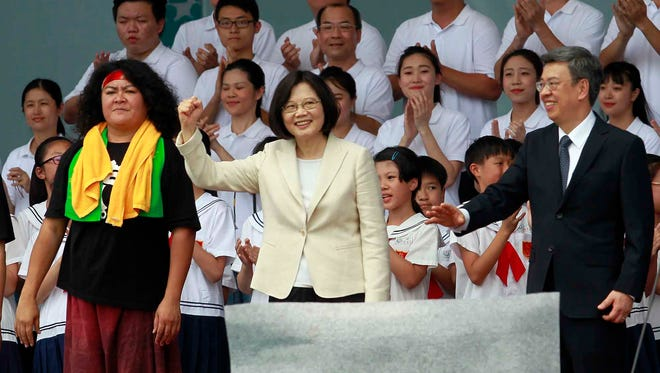 Taiwan's President Tsai Ing-wen, center, and her Vice President Chen Chien-jen, right, cheer the audience attending the inauguration ceremony in Taipei, Taiwan, Friday, May 20, 2016. Taiwan inaugurated Tsai its first female president on Friday, returning the pro-independence Democratic Progressive Party to power amid new concerns over increasingly fractious relations with Beijing and a flagging economy. (AP Photo/Chiang Ying-ying)