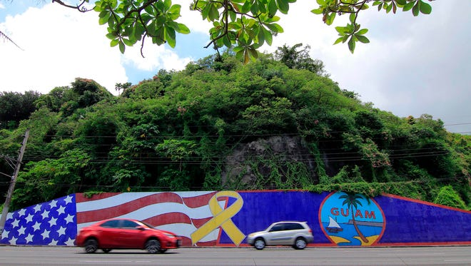 Afternoon traffic passes in front of a wall painted with U.S. and Guam flags in the Tumon district on the island of Guam on Friday, Aug. 11, 2017.