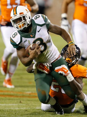 Miami (Fla.) running back Duke Johnson is stopped by Virginia safety Wilfred Wahee in Charlottesville, Va., on Nov. 22, 2014.