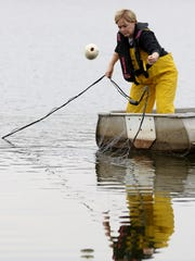 Renee Koerner casts a net at a lake in southeastern