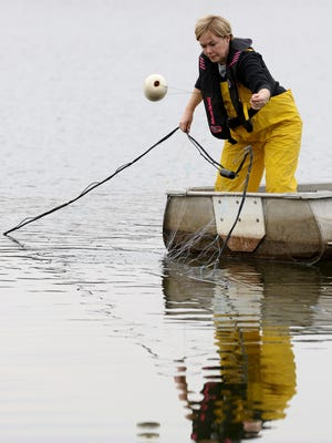 Renee Koerner casts a net at a lake in southeastern Hamilton County Tuesday February 21, 2017. Koerner uses the nets to catch paddlefish.  Ten years ago Koerner founded Big Fish Farms that produces farm-raised paddlefish products. The company sells caviar and the meat to local markets.