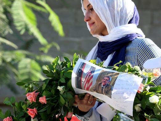 Salwa Bugaighis carries a wreath with a photo of U.S. Ambassador Chris Stevens as she and others pay their respects to the victims of an attack on the U.S. consulate, on Sept. 17, 2012, in Benghazi, Libya. Stevens and three other Americans were killed on Sept. 11 during the attack.