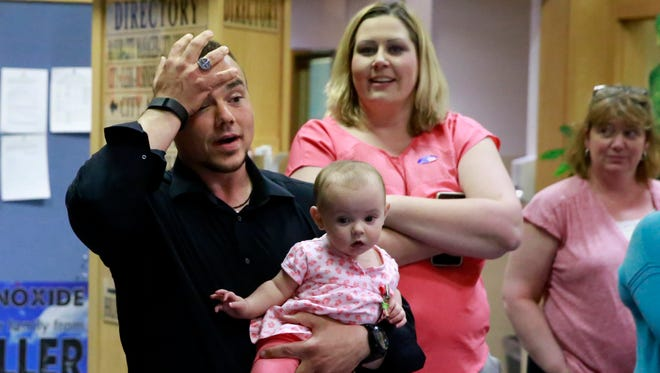 Sean Sharer, holding his seven-month-old daughter, Scarlett, reacts to initial poll results on Tuesday evening at Farmington City Hall that indicated he was winning the race for the District 2 seat on the Farmington City Council. Sharer went on to win the seat.