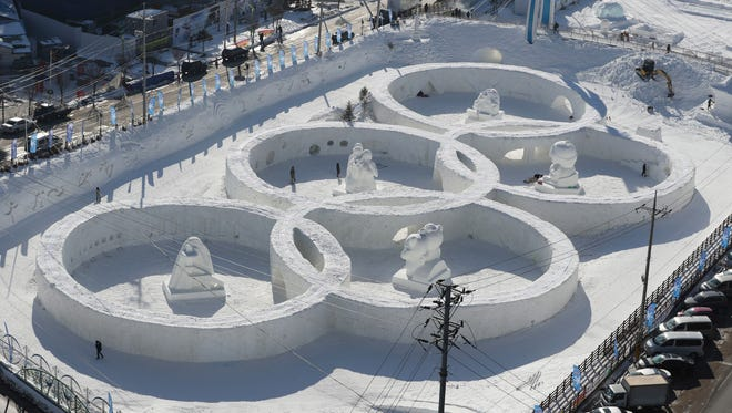 Visitors tour near the snow sculpture in the shape of the Olympic rings displaying at the Daegwanryung Snow festival in Pyeongchang, South Korea. South Korea's Pyeongchang is the host city of the 2018 Olympic and Paralympic Winter Games which will start from February 2018.