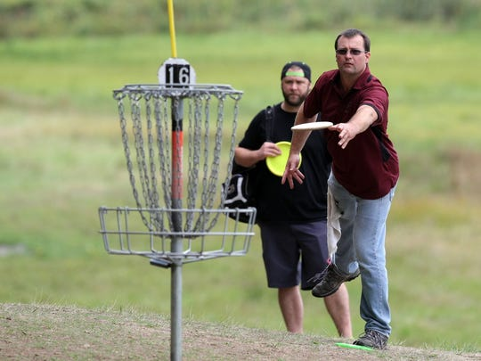 West Sound Disc Golf Championships event director Sam Huff tosses at the Bud Pell course in Silverdale. A group of Bainbridge Island disc golfers hopes to establish a course at Battle Point Park.