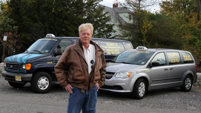 Gregory Hall, owner of Sandy's New Manasquan Taxi, stands next to two of his taxis in Manasquan.