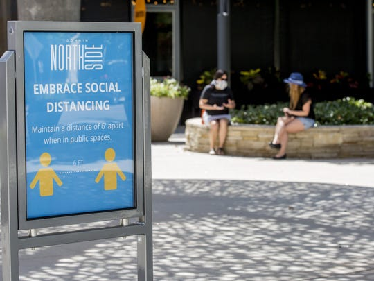 A sign encouraging social distancing can be seen at Domain Northside in Austin on Friday, May 1, 2020. Texas businesses are now allowed to open at 25% capacity during the first phase of Gov. Gregg Abbott's order to reopen the state amid the coronavirus outbreak.