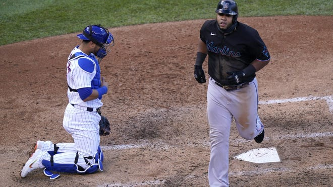 Chicago Cubs catcher Willson Contreras looks on as Miami Marlins slugger Jesus Aguilar crosses the plate after hitting a two-run home run off relief pitcher Jeremy Jeffress in the seventh inning of Game 1 of a National League wild-card baseball series Wednesday in Chicago.