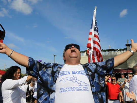 A member of the Cuban community celebrates the death of Fidel Castro, Saturday, Nov. 26, 2016, in the Little Havana area in Miami. Castro, who led a rebel army to improbable victory in Cuba, embraced Soviet-style communism and defied the power of 10 U.S. presidents during his half century rule, died at age 90.