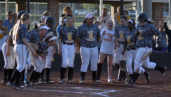 Hendersonville teammates greet Annsley Kalamon (far right) at home plate following her home run in the fourth inning of Tuesday's game against Station Camp.