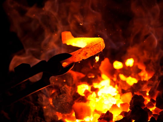 A horseshoe is pulled from a pile of burning coke ore