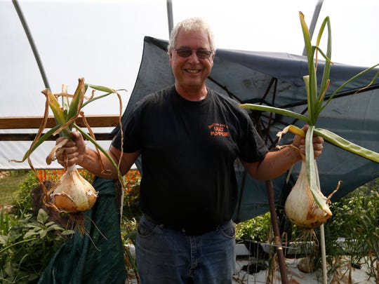 Marty Schnicker holds up a pair of onions Wednesday, Aug. 9, 2017, at his home near Mount Pleasant. Schnicker grows large vegetables to compete at the Iowa State Fair each year.