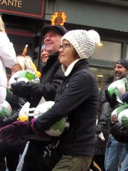 Costumed volunteers parade with donated turkeys Saturday