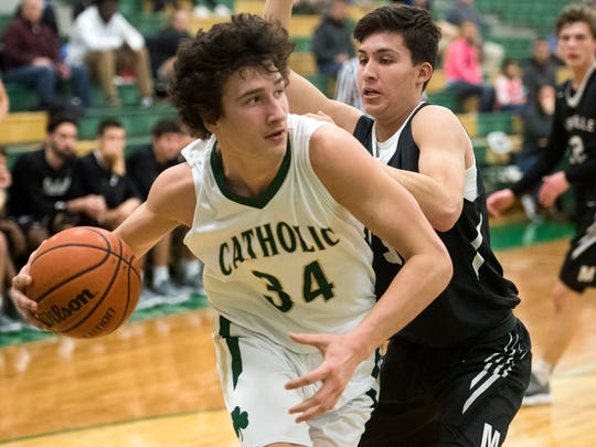 Knoxville Catholic's Brock Jancek is defended by Maryville's Emilio Cornelio in the boys basketball game on Monday, January 29, 2018.