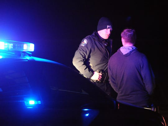 A Pickerington Police Officer talks to a passenger of a vehicle he stopped during a saturation patrol Wednesday night in Pickerington.