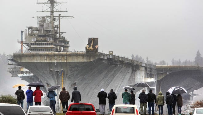 It was a gray and rainy morning as onlookers watch as the decommissioned aircraft carrier Independence pulls away from Naval Base Kitsap / Bremerton on Saturday. The ship is going to Brownsville, Texas for dismantling.
