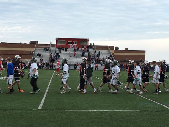 The Palmyra boys lacrosse team shakes hands with Trinity