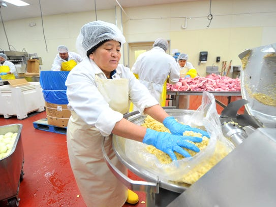Worker Mai Moua, 55, of Wausau, collects grounded garlic