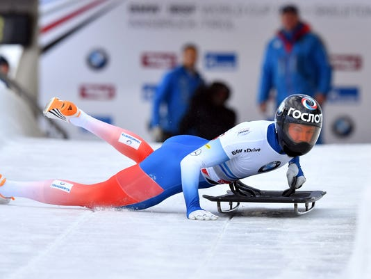 FILE - In this Dec. 15, 2017 file photo Russia's Alexander Tretiakov struggles to start his first run in the men's Skeleton World Cup race in Innsbruck, Austria. The Court of Arbitration for Sport ruled on Thursday, Feb. 1, 2018 to reinstate Tretiakov as gold medal winner of the men's skeleton at the 2014 Sochi Winter Olympics. (AP Photo/Kerstin Joensson, file)