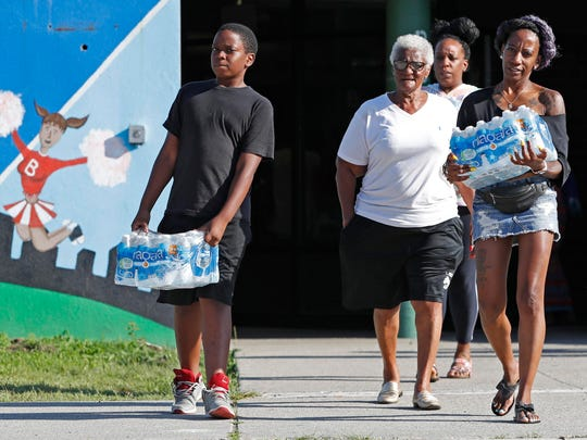 Rahjiah McBride, of Chester, Pa., right, helps her relatives, Newark residents Elnora and Bowdell Goodwin, center and second right, as Goodwin's son pitches in carrying bottled water from the Boylan Street Recreation Center on Monday in Newark, N.J.