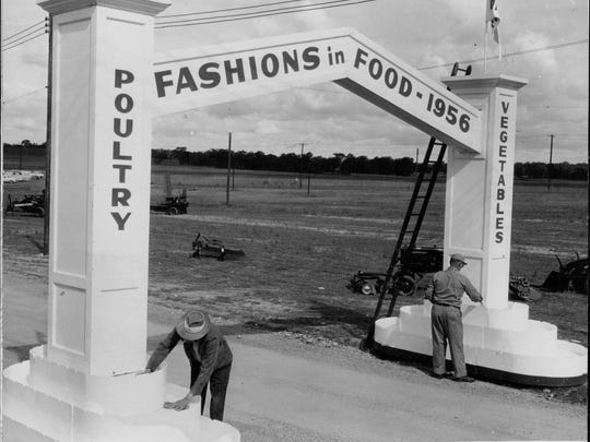 "Workmen paint the archway entrance to exhibit area. Fair opens tomorrow and closes Saturday. Harvest queens and alternates will dine tomorrow night at the barn."" Caption from 1956 photo."