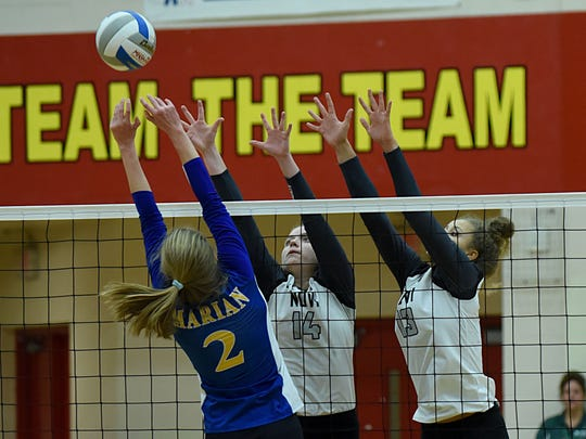 Marian's Jaeda Porter (14) and Erin O'Leary (13) try to block a kill from Marian's Maggie DePorre (2) in Tuesday's Class A state quarterfinal match.