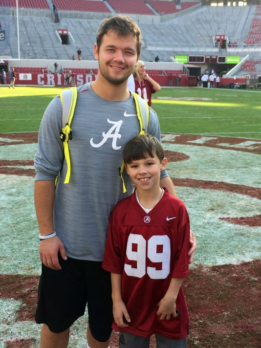 In this recent photo provided by Amy Murphree, Alabama kicker Adam Griffith, left, and Tupelo Bear flag football player Boone Murphree pose in Tuscaloosa, Ala. Both young men share unusual bonds, they are originally from Poland, they lived for a while in an orphanage and both were adopted by Southern families. The two have visited with each other and have established a friendship that Murphree takes seriously. (Amy Murphree via AP)