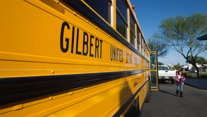 Gilbert Unifed School District bus stops to pick up a student.