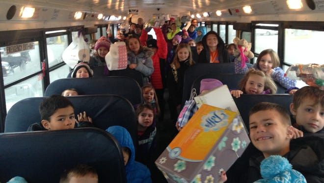 A bus full of Victor Primary and Intermediate School students hold their Stuff a Bus donations.
