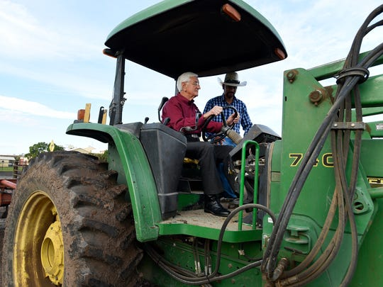 New Mexico State University Chancellor Garrey Carruthers uses a tractor to cut weeds in the field to the west of the Las Cruces Convention Center on Thursday, July 27, 2017. Paul Maese, NMSU farm ranch supervisor, directs Carruthers.